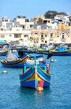 Fishing boats in Marsaxlokk harbour, Malta. Traditional Maltese Dghajsa fishing boats in the harbour with waterfront buildings to the rear, Marsaxlokk, Malta Royalty Free Stock Photo
