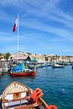 Fishing boats in Marsaxlokk harbour, Malta. Traditional Maltese Dghajsa fishing boats in the harbour with waterfront buildings to the rear, Marsaxlokk, Malta Stock Image