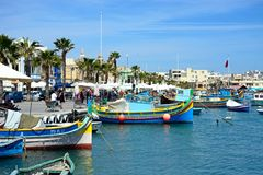 Fishing boats in Marsaxlokk harbour, Malta. Traditional Maltese Dghajsa fishing boats in the harbour with waterfront buildings and market stalls to the rear Royalty Free Stock Photo