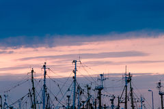 Fishing boats masts in port with sunset in background. Royalty Free Stock Photography