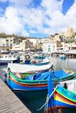 Fishing boats in Mgarr harbour, Gozo. Traditional fishing boats in the harbour with the Our Lady of Lourdes church on the hillside to the rear, Mgarr, Gozo Royalty Free Stock Photo