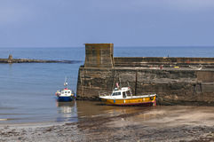 Fishing Boats Moored by Harbour Wall Stock Photography