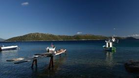 Fishing boats moored on Kalamos island. Video clip of fishing boats moored at sea moving with tide on Kalamos islanad, Ionian Islands, Greece stock footage