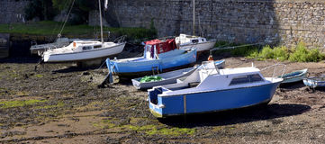 Fishing boats moored at low tide in the Cornish harbour. stock photo