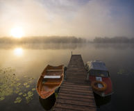 Fishing boats moored at the  small wooden bridge over the river. Oder river, Poland,fabulous sunrise on the river Royalty Free Stock Photos
