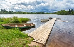 Fishing boats moored at a wooden pier on the lake. In summer day Royalty Free Stock Photo