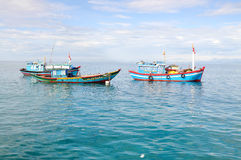 Fishing boats are mooring together in the sea Stock Images