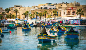 Fishing boats near fishing village of Marsaxlokk. Traditional fishing boats near market in fishing village of Marsaxlokk (Marsascala Royalty Free Stock Images