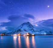 Fishing boats near pier on the sea and snowy mountains at night Royalty Free Stock Images