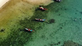 Fishing boats near reef. Beautiful aerial view of fishing boats floating on blue sea water near majestic coral reef stock video