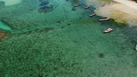 Fishing boats near reef. Beautiful aerial view of fishing boats floating on blue sea water near majestic coral reef stock footage