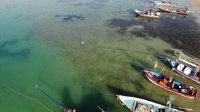 Fishing boats near shore. Various colorful fishing boats floating near coast on sea water in tropical country. Drone top stock video footage