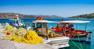 Fishing boats with nets at the pier in the village of Plaka in C Stock Photos