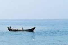 Fishing boats in the ocean. KOVALAM, INDIA - DEC 28, 2014: Traditional wooden fishing boats in the ocean. Kovalam. Kerala. India stock images