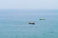 Fishing boats in the ocean. Traditional wooden fishing boats in the ocean. Kovalam. Kerala. India royalty free stock images