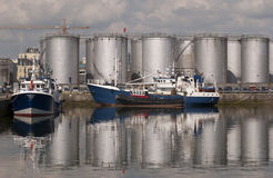 Fishing boats and oil storage tanks. Royalty Free Stock Photography