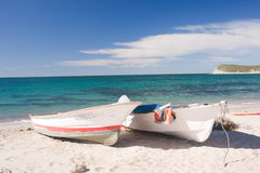 Fishing Boats on the Pacific Shore. Two fishing boats in the sand of the Pacific shoreline with the sea behind stock image
