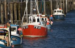 Fishing boats, Padstow, Cornwall, UK. Landscape image of fishing boats lined up along the harbour wall at Padstow, Cornwall, UK Stock Photography