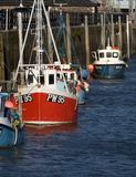 Fishing boats, Padstow, Cornwall, UK. Upright portrait shot of fishing boats lined up along the harbour wall at Padstow, Cornwall, UK Royalty Free Stock Photos