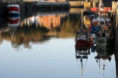 Evening light on fishing boats in Padstow harbour. Fishing boats in Padstow harbour in the evening with still calm water royalty free stock photo