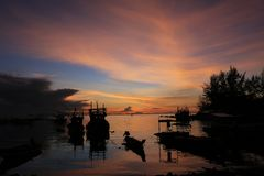 Fishing boat at sunset. Fishing boats parking on a bay at  evening sunset  before storm silhouette Stock Image
