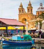 Fishing boats by pier near market and church in Marsaxlokk. Marsaxlokk, Malta - 24 May 2015: fishing boats luzzu by pier near market and church in Marsascala ( Stock Images