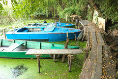 Fishing boats at pier. Several bright old-fashion fishing boats are docked at the wooden pier Royalty Free Stock Image