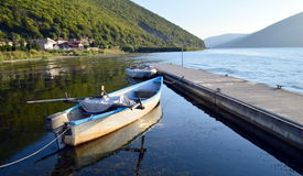 Fishing boats on a pier. Fishing boats and a pier in a small lakeside village in the greek region of Prespes Lakes stock images