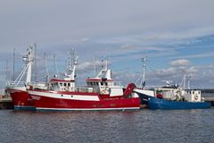 Fishing Boats in Port. Red and blue fishing boats in a small port Royalty Free Stock Images