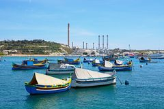 Fishing boats with the power station to the rear, Marsaxlokk. Traditional Maltese Dghajsa fishing boats in the harbour with Delimara power station to the rear Royalty Free Stock Image