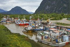 Fishing boats in Puerto Aysen, Patagonia, Chile. Colourful fishing boats in a creek in the coastal town of Puerto Aysen in northern Patagonia, Chile stock image
