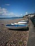 Boats pulled up onto the shore at Sidmouth in Devon. royalty free stock image