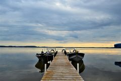Boats resting on Shawano lake in Wisconsin. Fishing boats resting on calm lake in Shawano northern Wisconsin in summertime with sunset and overcast skies in royalty free stock photos