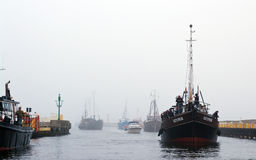 Fishing boats return. To port on a foggy day, loaded with fisherman, who were fisging with their fishing rods for cod. Baltic sea, Darlowo, Poland Royalty Free Stock Photo