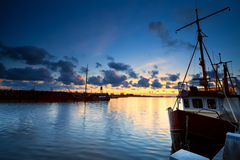 Fishing boats on river at sunset Stock Photos