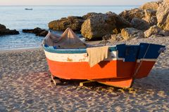 Fishing Boats and Rocks. Two fishing boats (one in the background) and rocky beach stock photography