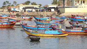 Fishing boats roll in bay against small village at dawn. Vietnamese fishing boats with colourful banners roll in sea bay against fishing village at dawn stock footage