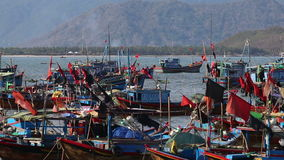 Fishing boats roll in sea   bay against mountains at dawn. Vietnamese fishing boats with colourful banners roll on sea water in bay against mountains at dawn stock video footage