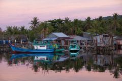 Fishing boats in rural area of Phu Quoc Island. Fishing boats near houses of fishermen in rural area of Phu Quoc Island, Southern Vietnam Stock Image