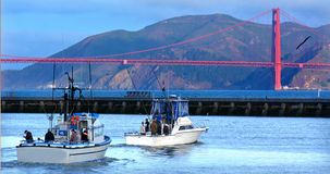 Fishing boats sail out of Fisherman wharf in San Francisco - CA Royalty Free Stock Photo