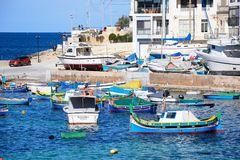 Fishing boats in San Pawl harbour, Malta. Traditional Maltese Dghajsa fishing boats moored in the harbour with town buildings to the rear, San Pawl, Malta Stock Photography
