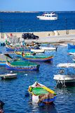 Fishing boats in San Pawl harbour, Malta. Traditional Maltese Dghajsa fishing boats moored in the harbour with views towards the coastline, San Pawl, Malta Stock Photos