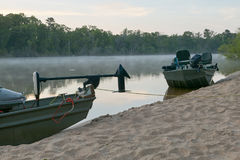 Fishing boats on the sandy bank of Altamaha River. Two fishing boats moored on sand on the banks of the Altamaha River in Georgia at sunset Stock Photo