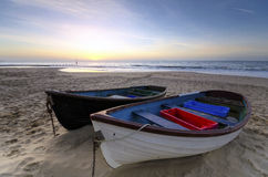 Fishing Boats on a Sandy Beach. Fishing boats on the sand at Bournemouth beach in Dorset at sunrise Stock Photos