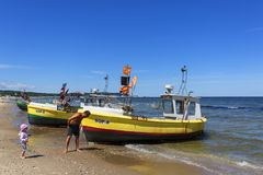 Fishing boats by the sandy beach on the Baltic Sea on a sunny day, Sopot, Poland. SOPOT, POLAND - JUNE 6, 2018: Fishing boats by the sandy beach on the Baltic stock photo