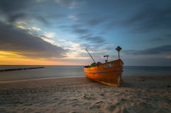 Fishing boats on the sea beach during sunset Stock Image