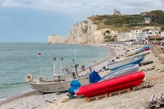 Fishing boats and seaside visitors at beach Etretat, Normandie, France Royalty Free Stock Images