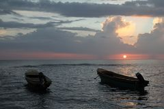 South Jamaica Travel. Fishing boats are seen from the shore at dusk in Treasure Beach, Jamaica Stock Image