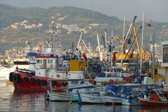 Fishing boats in a harbor. Fishing boats and ships in a harbor, mountain in the background Stock Images