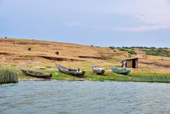 Kazinga Channel, Queen Elizabeth National Park, Uganda. Fishing boats shown on the Kazinga channel shore at twilight. The Kazinga channel is the only source of Stock Photos